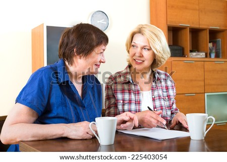 Two elderly friends sitting at a table and signing documents - stock photo