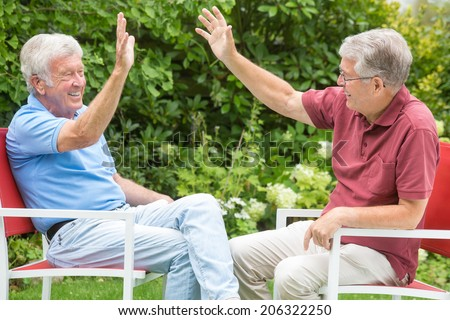 Two elderly men are sitting opposite and are having so much fun they high-five each other - stock photo