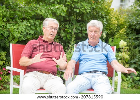 Two elderly men are sitting, the left one is explaining something to the right one who is listening attentively - stock photo