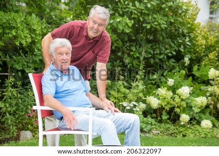 Two elderly men are smiling into the camera, one man is bending down to the other - portrait