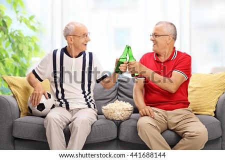 Two elderly men watching a game of football and drinking beer at home