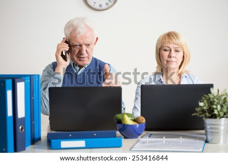 Two elderly people having their own company - stock photo