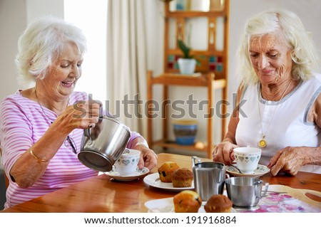 Two elderly women having tea and muffins together - stock photo