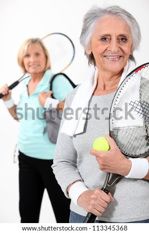 Two elderly women playing tennis - stock photo