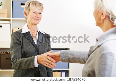 Two elderly women shaking hands after meeting in the office - stock photo
