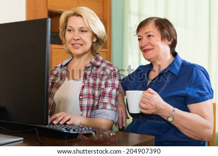 Two elderly women sitting in front of PC with coffee and laughing - stock photo