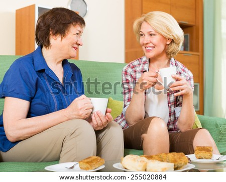 Two elderly women sitting on sofa and gossiping with cup of tea in home interior - stock photo