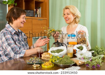 Two elderly women with medicinal herbs brewing herbal tea - stock photo