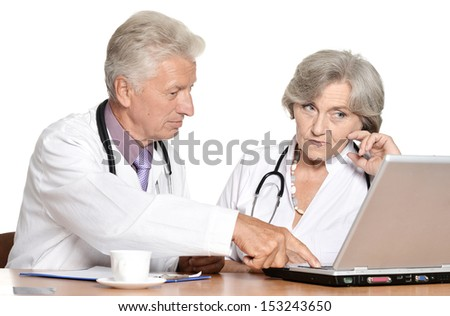 Two eldery doctors have a discussion at table - stock photo