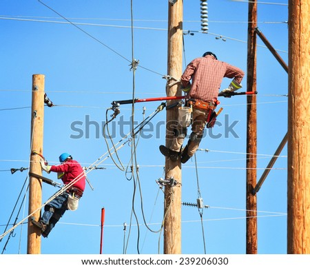two electrical linemen working on lines - stock photo