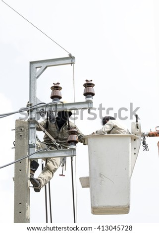 Two electrician are installing new cables of high voltage that one electrician is climbing on an electric power pole, another one  is on lift bucket - stock photo