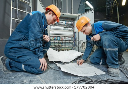 two electrician builder engineer with blue print scheme project in front of fuse switch box - stock photo
