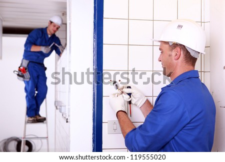 Two electricians working - stock photo