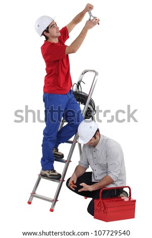 Two electricians working together - stock photo