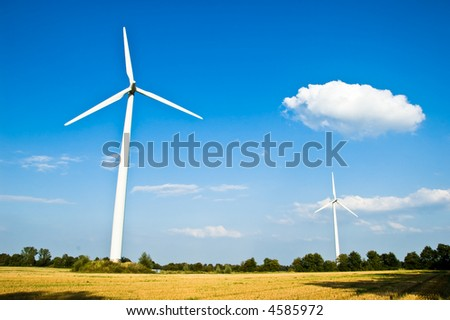 Two electricity generating windmills in a field