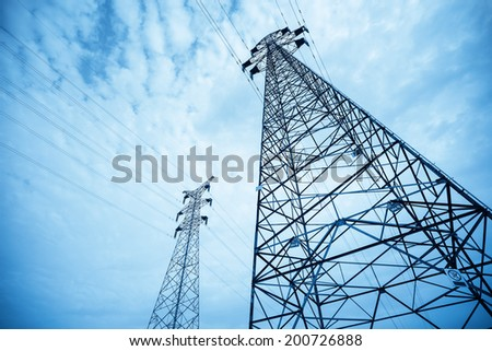two electricity pylons against the blue sky  - stock photo