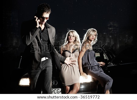 Two elegant blond ladies watching a man calling - stock photo