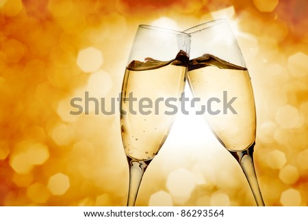 Two elegant champagne glasses on golden background