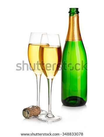 Two elegant champagne glasses on the background of green bottles close-up isolated on  a  white. Festive still life. - stock photo