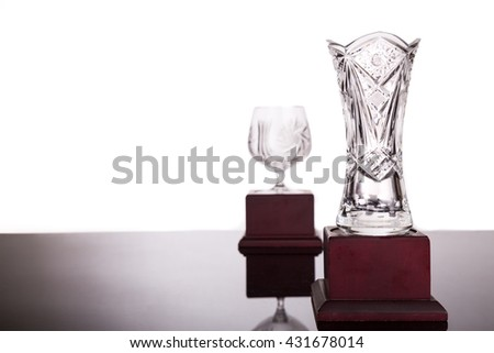 Two elegant crystal trophies with focus on vase trophy at foreground - stock photo