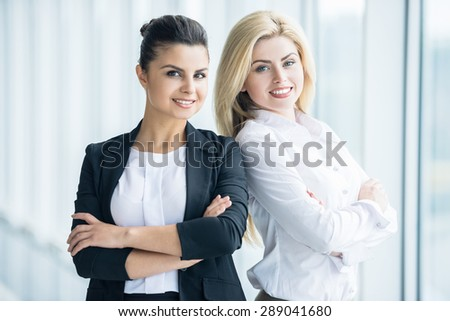 Two elegant female office workers standing back to back and smiling to camera. - stock photo