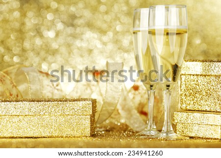 Two elegant flutes of sparkling champagne with decorative golden gifts - stock photo
