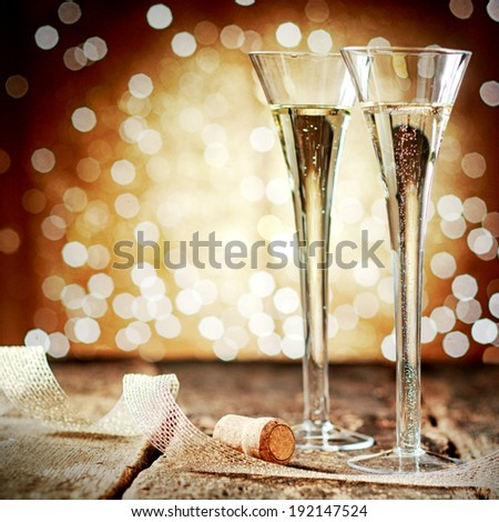 Two elegant flutes of sparkling golden champagne with twirled decorative ribbon against a bokeh of twinkling party lights at a festive celebration - stock photo