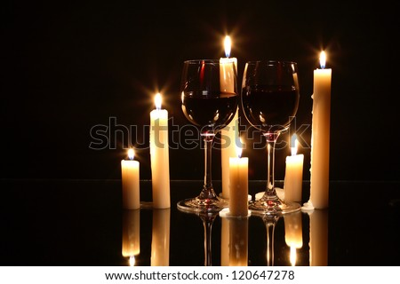 Two elegant goblets of red wine near lighting candles on dark background - stock photo