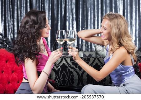 Two elegant happy girls in the restaurant drinking wine - stock photo