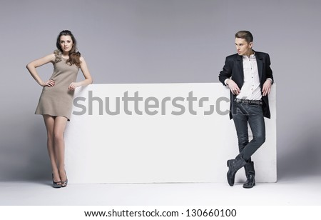 Two elegant people next to big white board - stock photo
