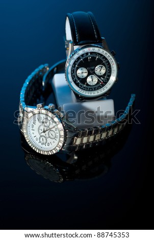 Two elegant watches  for womans and mans on black background  with blue light - stock photo