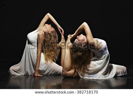two elegant women dancing in long white dresses - stock photo