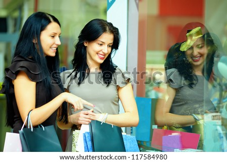 two elegant women look in clothes store showcase