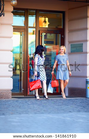 two elegant women shopping in city mall