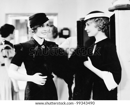 Two elegant women standing together in a department store - stock photo