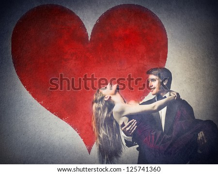 Two elegant young lovers dancing with a big heart drawn on a wall in the background - stock photo