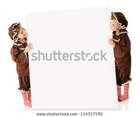 Two elementary gingerbread girls looking across a large white sign (left blank for your text) at each other.  On a white background. - stock photo