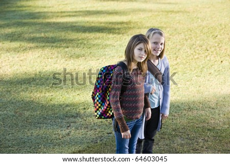 Two elementary school girls (10 and 11 years) carrying their bookbags