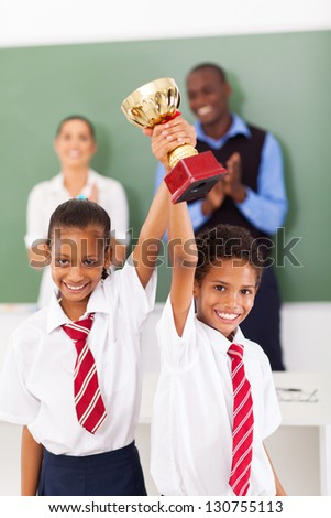 two elementary students holding a trophy in classroom