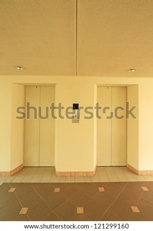 Two elevator doors and decorative tiled floor - stock photo