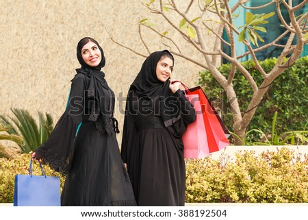 Two Emarati Arab women coming out of shopping with bags in her hand in Dubai, United Arab Emirates. - stock photo