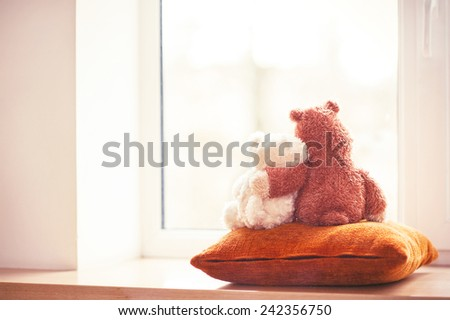 Two embracing teddy bear toys  looking through the window sitting on window-sill. Filtered image. Indoors - stock photo