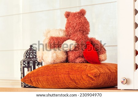 Two embracing teddy bears in love looking through the window sitting on window-sill. - stock photo