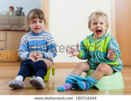 Two emotional siblings sitting on chamber pots in home interior - stock photo