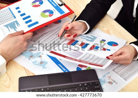 Two employees discussing business chart in office. Close up
