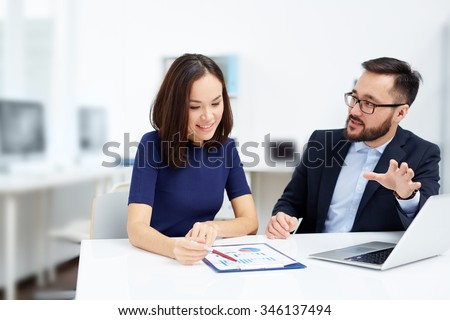 Two employees discussing document at meeting - stock photo