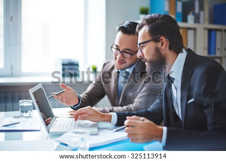 Two employees discussing electronic data at meeting - stock photo
