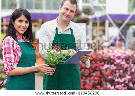Two employees doing inventory in garden centre wth tablet pc - stock photo