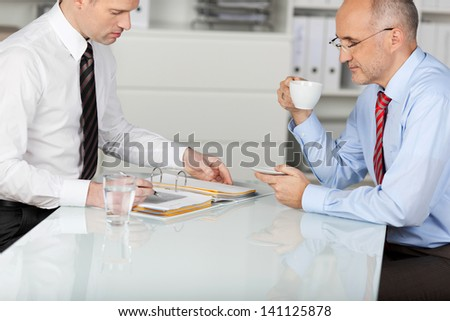 Two employees having a coffee while searching something in binder - stock photo
