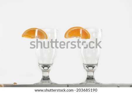 Two empty glasses of cocktails with the slice of orange standing on the bar counter - stock photo